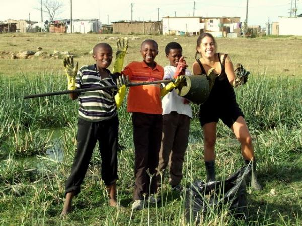 Photo of student with local children in South Africa